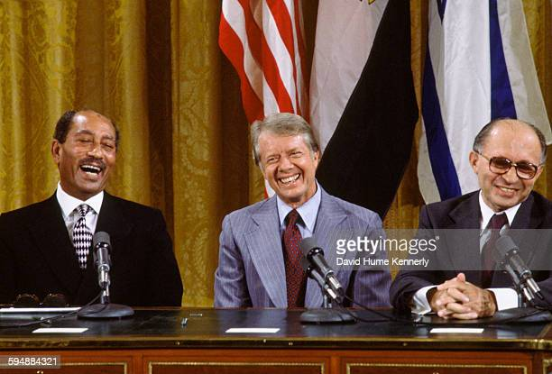 Egyptian President Anwar alSadat US President Jimmy Carter and Israeli Premier Menachem Begin laugh together during the signing the Camp David...