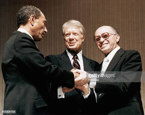 Egyptian President Anwar as-Sadat, US President Jimmy Carter and Israeli Prime Minister Menachem Begin shake hands at the signing of the Camp David...