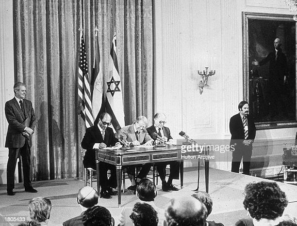 Egyptian president Anwar elSadat US president Jimmy Carter and Israeli prime minister Menachem Begin sign the Egyptian Israeli peace agreement at the...