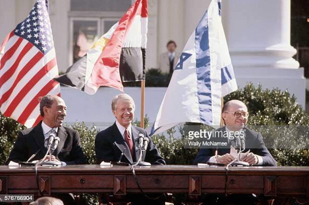 Egyptian president Anwar elSadat US President Jimmy Carter and Israeli Prime Minister Menachem Begin sit together in the sunshine outside the White...