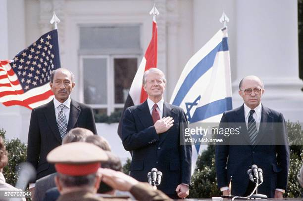 Egyptian President Anwar elSadat US President Jimmy Carter and Israeli Prime Minister Menachem Begin stand for the three countries' national anthems...