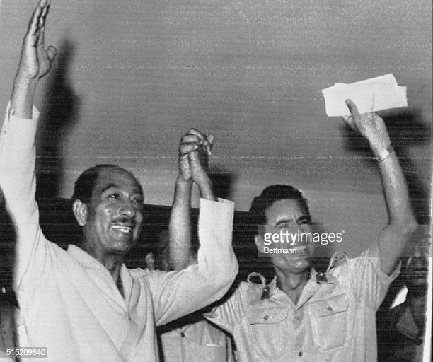 Egyptian President Anwar Sadat and Libyan strongman Colonel Muammar alQaddafi wave to the crowd in Benghazi Libya August 2 after they announced an...