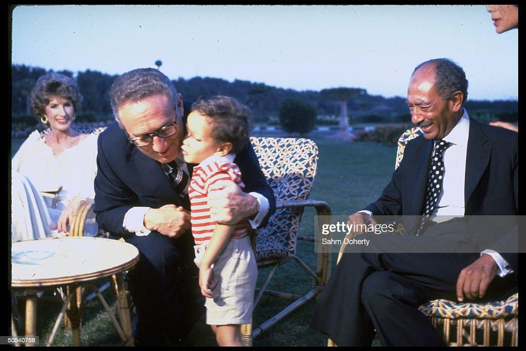 Egyptian President Anwar Sadat (1918 - 1981) (R) and Nancy Kissinger looking on as the former US Secretary of State Henry Kissinger hugs Sadat's grandson Sharif while they sit outside, Alexandria, Egypt, July 1979.