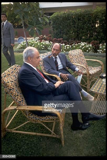 Egyptian President Anwar Sadat and US Ambassador Robert Strauss talking as they sit outside