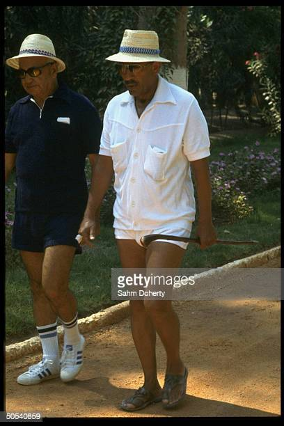 Egyptian President Anwar Sadat going for daily twomile walk with friend and confidant Osman Ahmed Osman