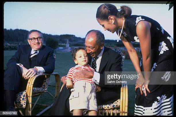 Egyptian President Anwar Sadat hugging grandson Sharif as daughter Noha and the former US Secretary of State Henry Kissinger look on outside