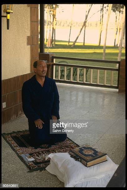 Egyptian President Anwar Sadat praying on back porch of his house
