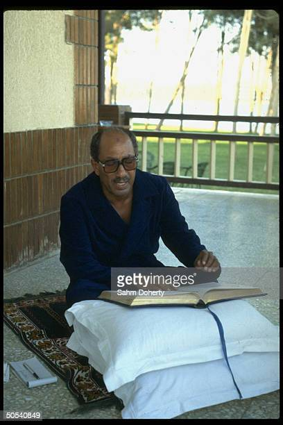 Egyptian President Anwar Sadat reading the Koran while praying on back porch of his house