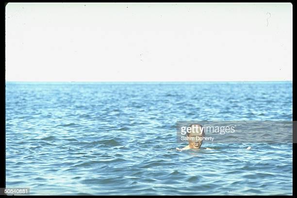Egyptian President Anwar Sadat swimming in the Suez Canal