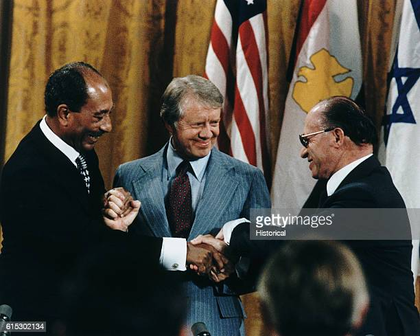 Egyptian President Anwar Sadat, U.S. President Jimmy Carter, and Israeli Prime Minister Menachem Begin shake hands after signing the peace treaty...