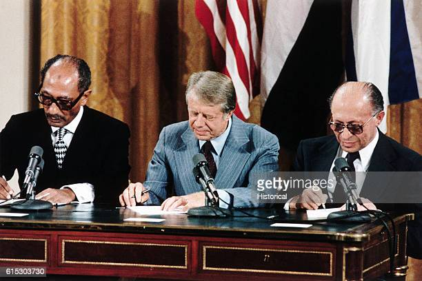 Egyptian President Anwar Sadat US President Jimmy Carter and Israeli Prime Minister Menachem Begin sign the peace treaty between Israel and Egypt in...