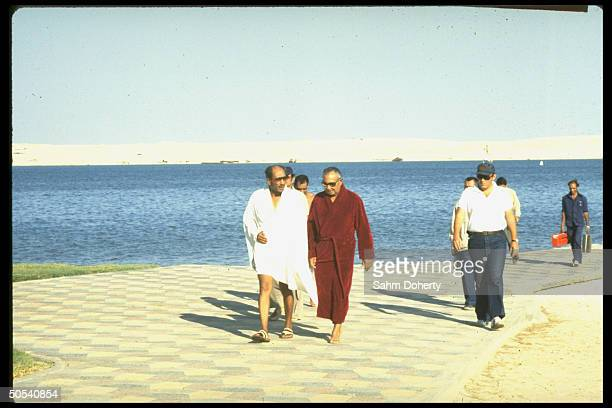 Egyptian President Anwar Sadat walking with friend and confidant Osman Ahmed Osman on a dock