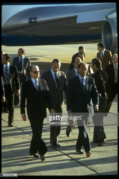 Egyptian President Anwar Sadat walking with the Shah of Iran down runway at the airport upon the Shah's arrival in Egypt.
