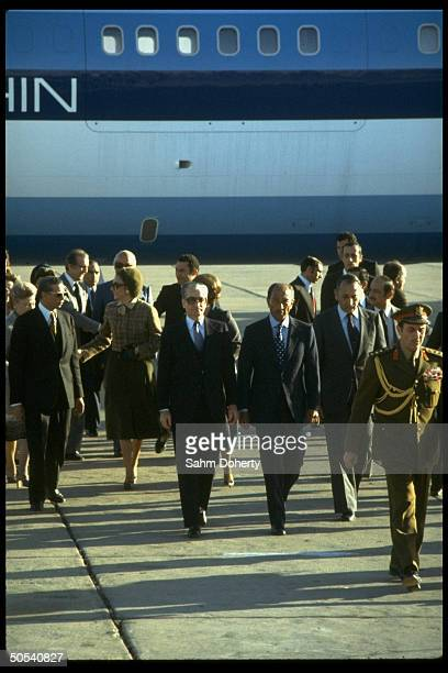 Egyptian President Anwar Sadat walking with the Shah of Iran down runway at the airport upon the Shah's arrival in Egypt
