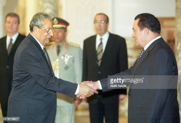 Egyptian President Hosni Mubarak shakes hand with his new Prime Minister Atef Ebeid 11 October 1999 in Cairo Mubarak chaired the first meeting of a...