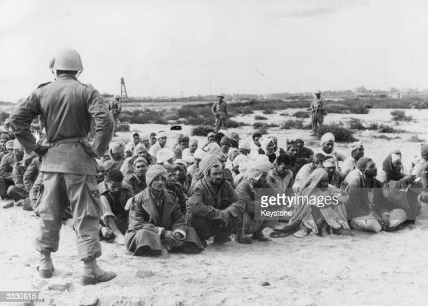 Egyptian prisoners are guarded by French soldiers as they sit on the beach of FortFouad Egypt during the Suez crisis