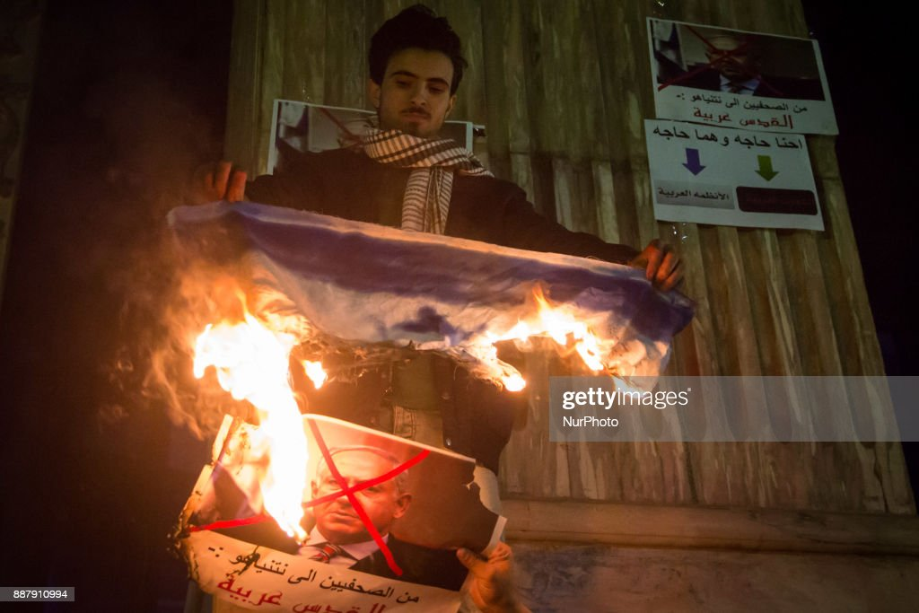 Egyptian protesters burn an Israeli flag and portrait of Israeli Prime Minister Benjamin Netanyahu during a demonstration against the US president's recognition of Jerusalem as Israel's capital, on December 7, 2017, outside the Syndicate of Journalists Cairo's downtown district.