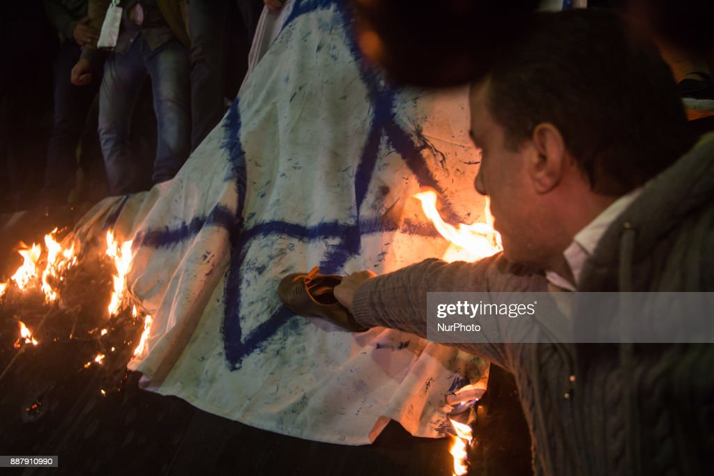 Egyptian protesters burn and put a shoe on an Israeli flag during a demonstration against the US president's recognition of Jerusalem as Israel's capital, on December 7, 2017, outside the Syndicate of Journalists Cairo's downtown district.