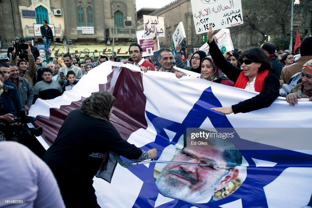 Egyptian protesters carry a banner showing Egyptian President Mohammed Morsi's face on an Israeli flag, flanked by the flags of the United States and Qatar, during a protest march February 11, 2013 in Cairo, Egypt. Protests continued across Egypt against President Morsi and the Muslim Brotherhood on the 2nd anniversary of former President Hosni Mubarak stepping down, and over two weeks after the second anniversary of the Egyptian Revolution beginning on January 25, 2011. (Photo by Ed Giles/Getty Images).