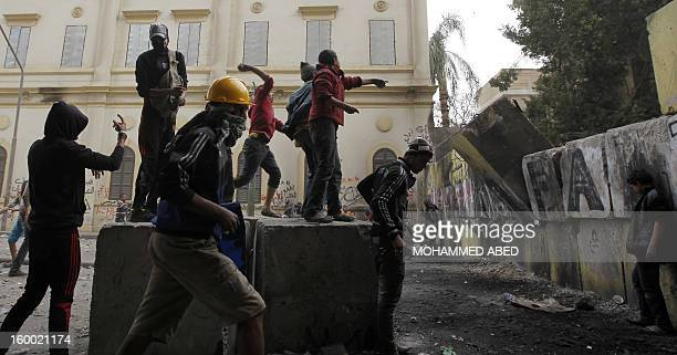 Egyptian protestErs dismantle a cement security barrier built to protect the parliament of the cabinet building near Tahrir Square during a protest...