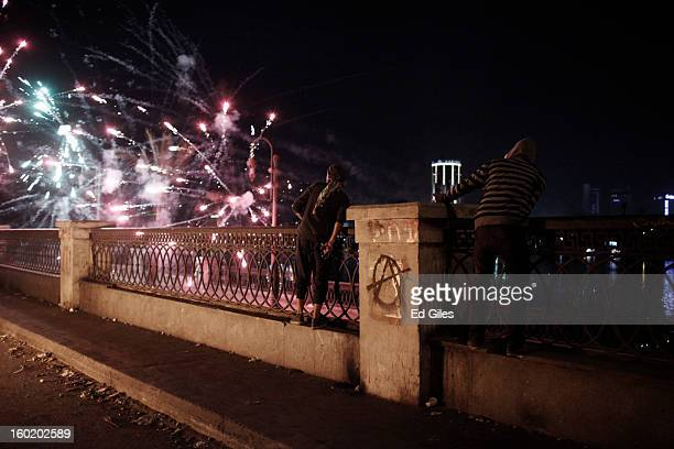 Egyptian protesters look on as fireworks shot toward nearby riot police explode during clashes near Tahrir Square on January 27 2013 in Cairo Egypt...