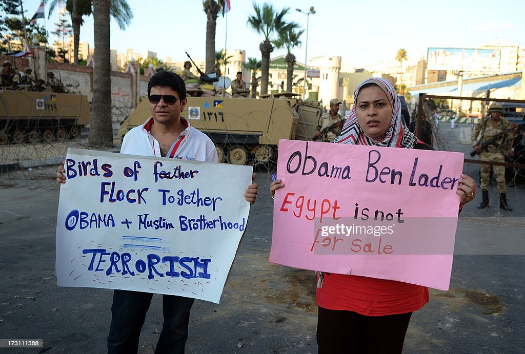 Egyptian protesters pose with placards reading slogans against US President Barack Obama during a demonstration against deposed president Mohamed Morsi on July 7, 2013 in the northern Egyptian city of Alexandria. In the capital, opponents of Morsi packed Tahrir Square in their tens of thousands to show the world his ouster was not a military coup but the reflection of the people's will.