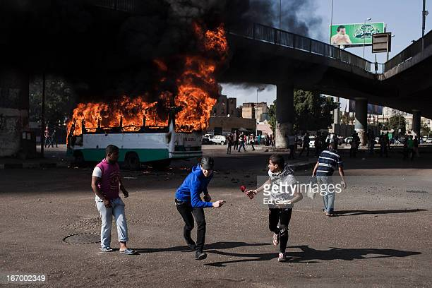 Egyptian protesters run away from a burning bus set alight during violent clashes between supporters of Egyptian President Mohammed Morsi and...