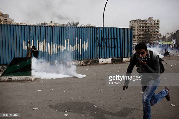 Egyptian protesters run away from tear gas canisters fired by riot police during a demonstration in Tahrir Square on January 27 2013 in Cairo Egypt...
