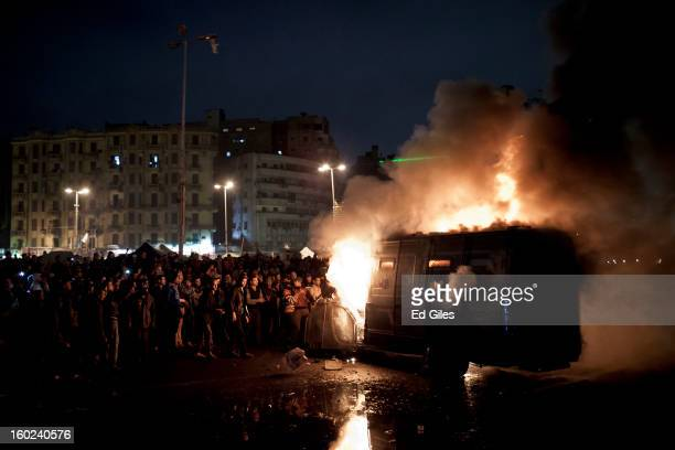 Egyptian protesters stand by an armoured Egyptian riot police vehicle of the or Central Security Forces that had been stolen then set alight during...