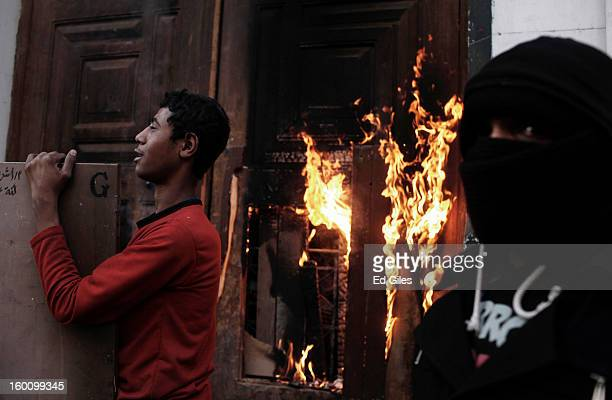 Egyptian protesters stand by the burning door of a school building during a protest following the announcement of the death penalty for 21 suspects...