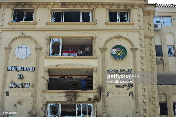 Egyptian protesters stand in the burnt headquarters of the Muslim Brotherhood in the Moqattam district of Cairo on July 1, 2013 after it was set...