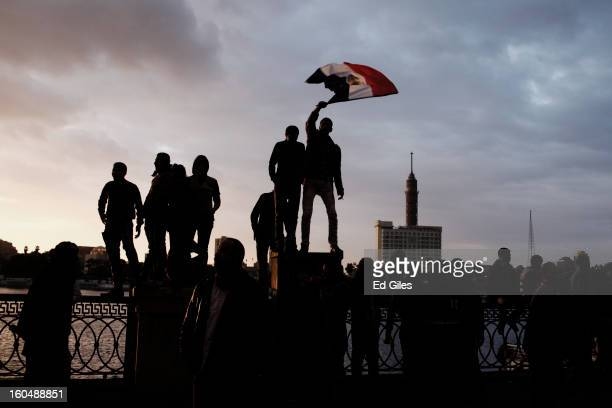Egyptian protesters stand on a fence by the River Nile during a protest against Egyptian President Mohammed Morsi near Tahrir Square on February 1,...