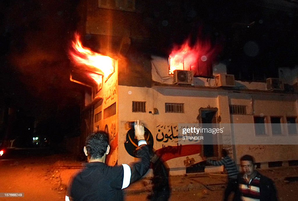 Egyptian protesters stand outside the burning office of the Muslim brotherhood in Ismailia, Egypt, on December 5, 2012 . Supporters and opponents of Egypt's President Mohamed Morsi lobbed firebombs and rocks at each other as their standoff over his expanded powers and an Islamist-drafted constitution turned violent.
