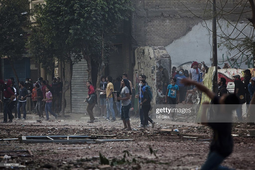 Egyptian protesters throw rocks toward Egyptian riot police during violent protests near Tahrir Square, on November 23, 2012 in Cairo, Egypt. Thousands of Egyptian protesters gathered in central Cairo's Tahrir Square on Friday to protest against a new constitutional declaration issued yesterday by Egyptian president Mohammed Morsi, giving him sweeping powers, and extending the period of deadline for the drafting of Egypt's new constitution by two months. The seven-article declaration renders the president's decrees and laws immune from appeal or cancellation. It also protects both Egypt's Shura Council and Islamist-dominated Constituent Assembly from dissolution by the country's judicial authorities. The demonstration follows a week of violent protests in central Cairo, commemorating one year since a series of deadly protests named 'Mohammed Mahmoud', after the street they took place in, during November 2011.