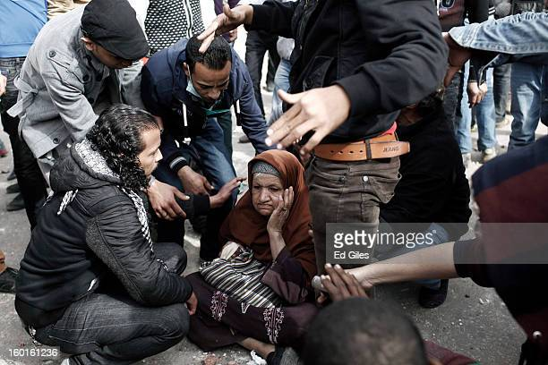Egyptian protesters try to convince an elderly woman to move out of the way after sitting down in between opposing sides during a demonstration in...