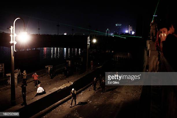 Egyptian protesters walk under an overpass toward nearby riot police during clashes near Tahrir Square on January 27 2013 in Cairo Egypt Violent...