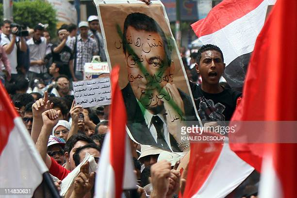 Egyptian protesters wave their national flag and carry a crossedout picture of ousted president Hosni Mubarak during a demonstration in Cairo on May...