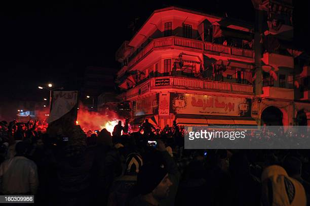 Egyptian protestors light up a flare as they demonstrate in the streets of the canal city of Port Said late on January 28 breaking the curfew the...
