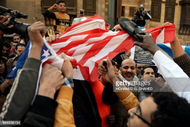 Egyptian protestors prepare to burn an American flag during a demonstration against US President Donald Trump's decision to recognize Jerusalem as...