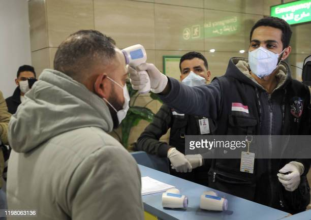 Egyptian Quarantine Authority employees scan body temperature for incoming travellers at Cairo International Airport on February 1 amidst efforts to...