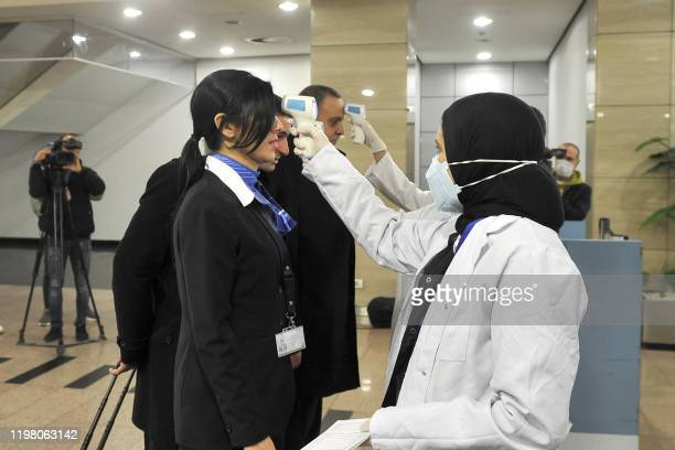 Egyptian Quarantine Authority employees scan body temperature for incoming flight attendants at Cairo International Airport on February 1 amidst...