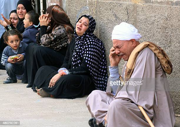 Egyptian relatives of supporters of ousted Islamist president Mohamed Morsi cry sitting outside the courthouse on March 24, 2014 in the southern...