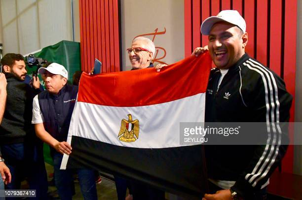 Egyptian representatives pose with their national flag as they celebrate the Confederation of African Football executive committee's decision to...