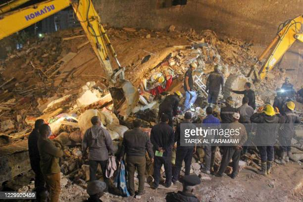 Egyptian rescuers and bystanders are pictured at the site where a dilapidated building collapsed in the Egyptian city of Alexandria, early on...