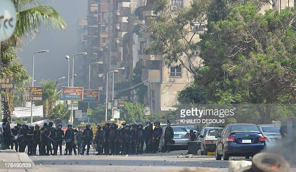 Egyptian riot police are seen in a street leading to a camp of supporters of Egypt's ousted president in Cairo's Rabaa al-Adawiya as they try to...