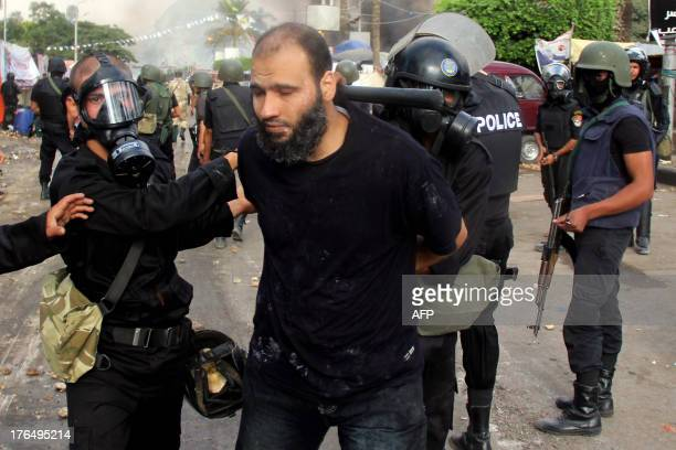 Egyptian riot police arrest a demonstrator in Cairo's al-Nahda square as they dispersed supporters of Egypt's ousted president Mohamed Morsi in two...