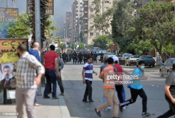 Egyptian riot police chase Muslim Brotherhood supporters as they try to disperse pro-Morsi demonstrators in a street leading to the Rabaa al-Adawiya...