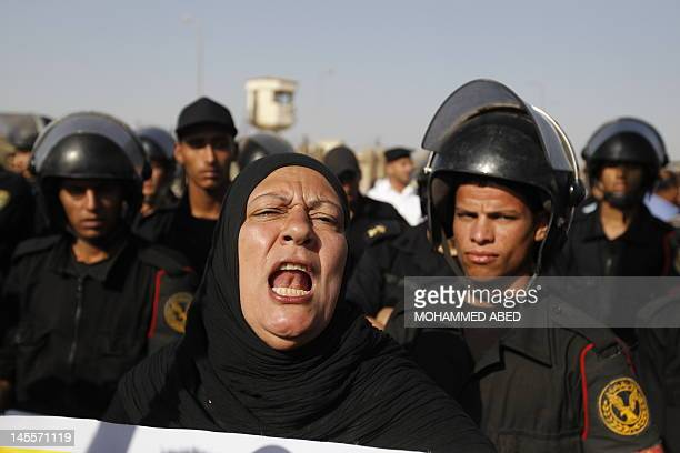 Egyptian riot police stand guard outside a Cairo court as protesters shout slogans against former president Hosni Mubark on June 2 ahead of a verdict...
