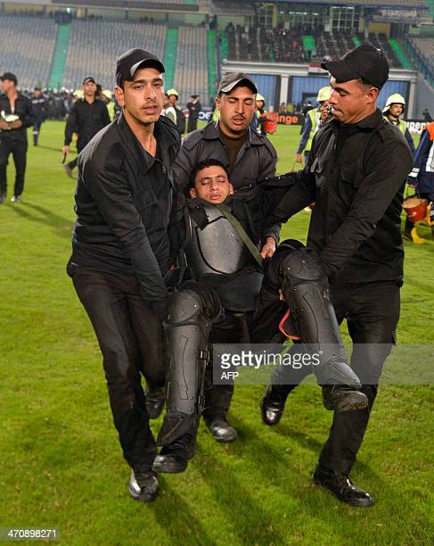 Egyptian riot policemen carry one of their comrades who was injured during clashes with supporters after Egypt's AlAhly won the African Super cup...