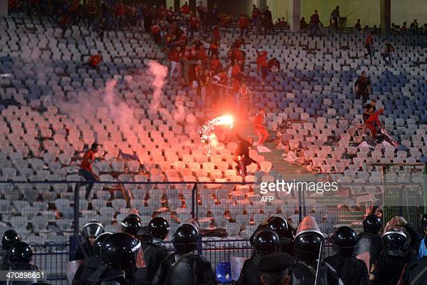 Egyptian riot policemen face supporters one throwing a flare during clashes after Egypt's AlAhly won the African Super cup final football match...